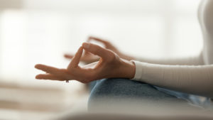 A person sitting and meditating and learning how to be mindful.
