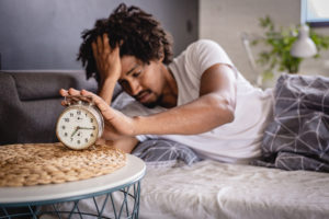 Man being woken up by clock-how to be mindful during times of stress.